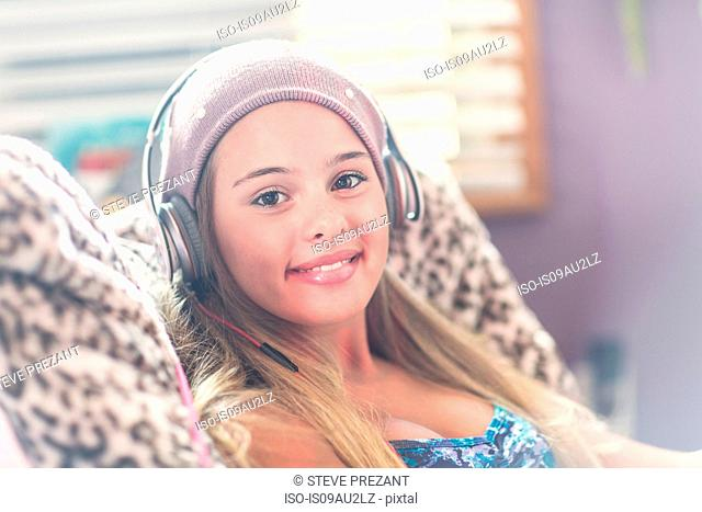 Teenager with earphones smiling on lazy chair