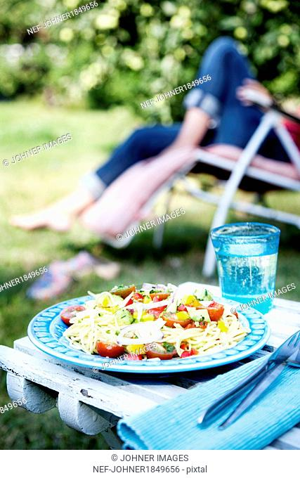 Salad on plate, woman on sun chair in background