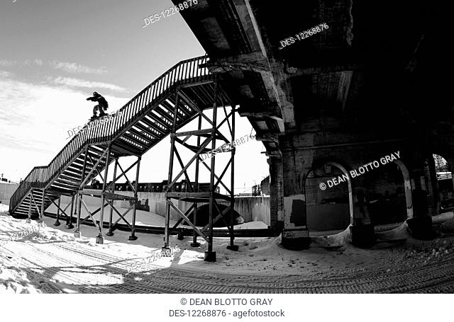Snowboarder balancing on the handrail of steps; Minnesota, United States of America
