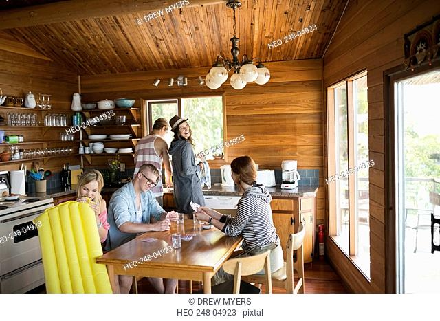Young friends playing cards at cabin kitchen table