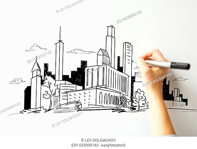 people, graphic arts and architecture concept - close up of hand with marker drawing city sketch on white board or paper