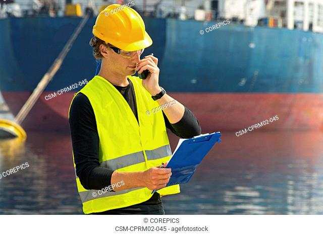 Engineer, reading out instructions from the notes on his clipboard over the radio