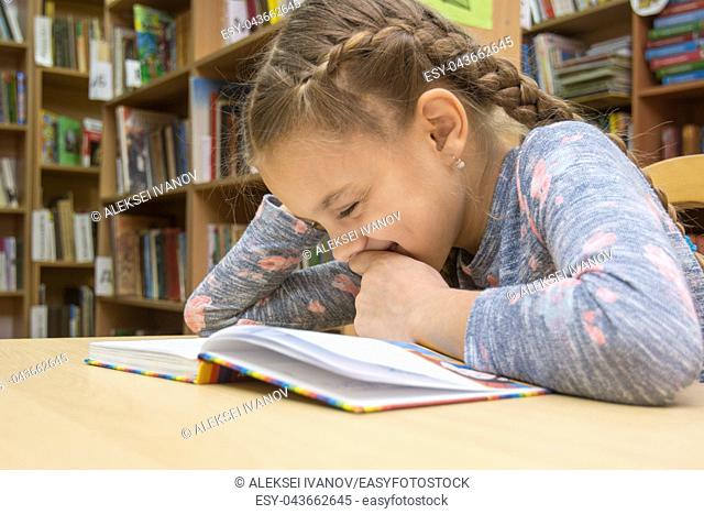 Girl laughing while reading a book in the library