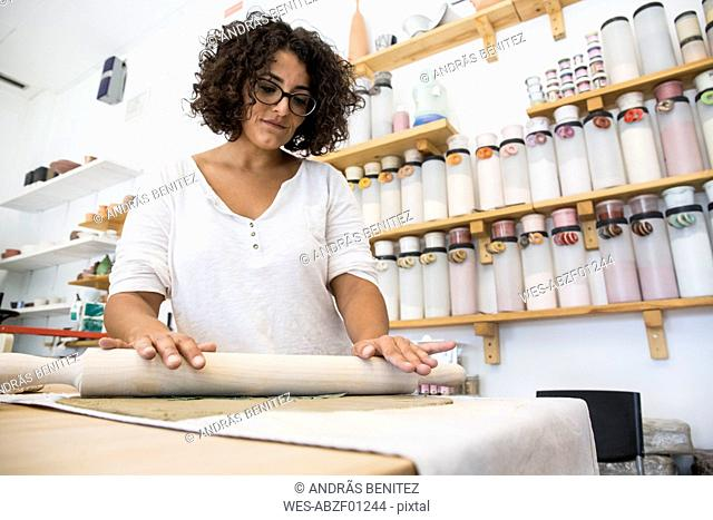Woman using a roller to work with terracota in a ceramics workshop