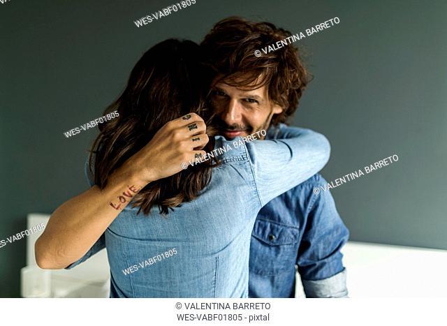 Smiling tattooed man embracing girlfriend