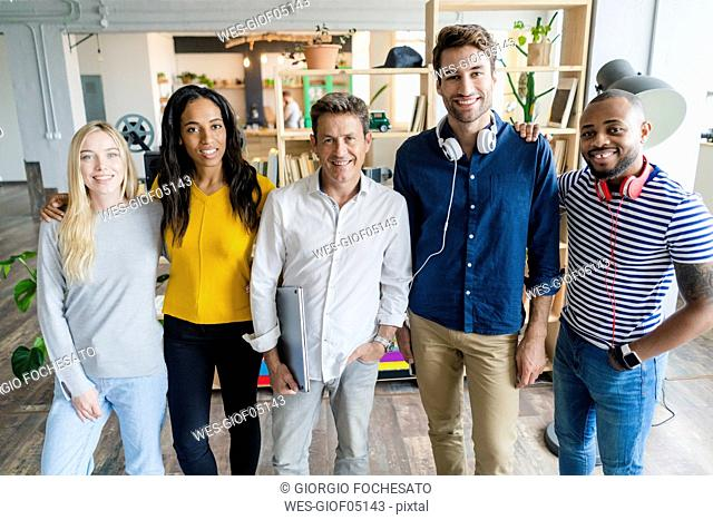 Portrait of confident business team standing in loft office
