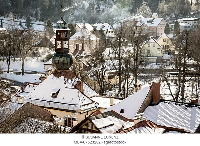 View of snow-covered town houses with smoking chimneys, from above, Murau, on a sunny winter day