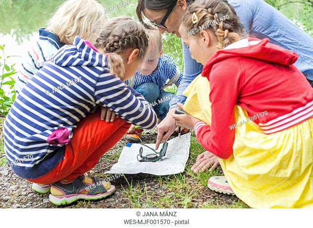 Germany, Children learning how to use compass and map