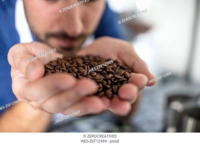 Man smelling handful of coffee beans