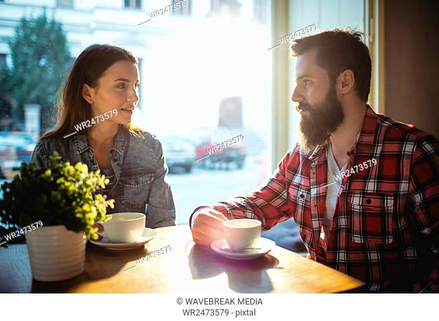Young couple communicating at cafe