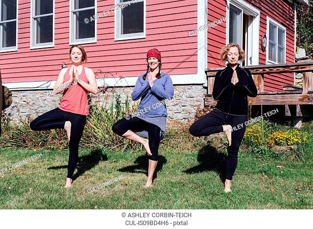 Three women practicing yoga tree pose (vriksasana) in garden