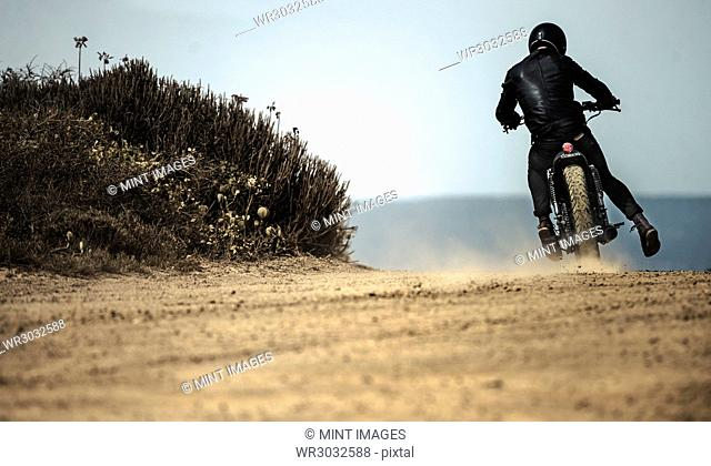 Rear view of man wearing crash helmet and black leathers riding cafe racer motorcycle on a dusty dirt road
