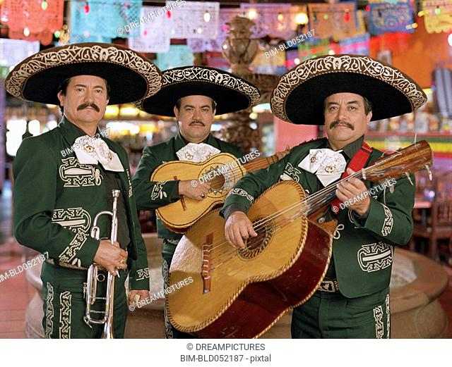 Hispanic mariachi musicians holding instruments