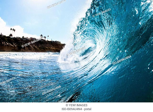 Surface level view of rolling ocean wave and coastline. Encinitas, California, USA