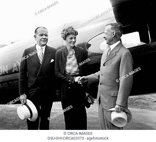 Amelia Earhart, Center, Portrait Shaking Hands with Man in front of Airplane, Harris & Ewing, 1932