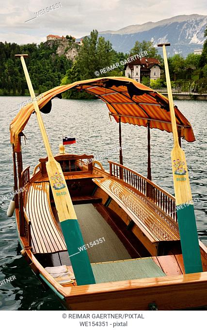 Traditional hand crafted wood Pletna boat with painted oars and canopy on Lake Bled with Bled castle and Vila Preseren Slovenia