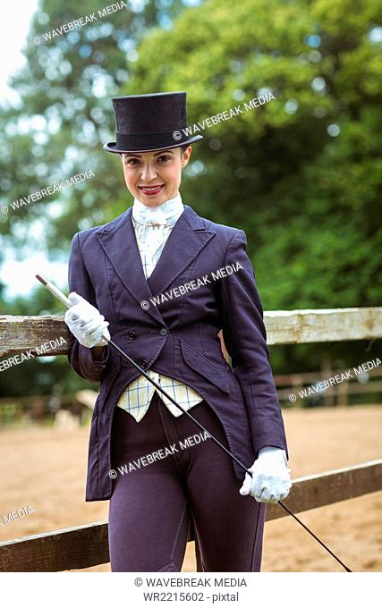 Smiling jockey with whip posing for camera