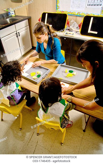 A teacher watches as blind children use yellow and green gel to signify lemon and lime -- both starting with the letter 'L' -- to form the letter 'L' by touch...