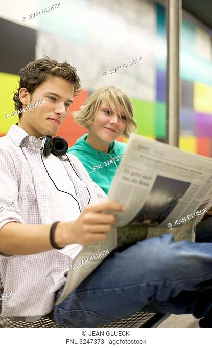 Teenager couple readung newspaper at underground, low-angle view