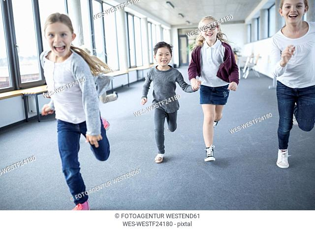 Excited schoolgirls rushing down school corridor