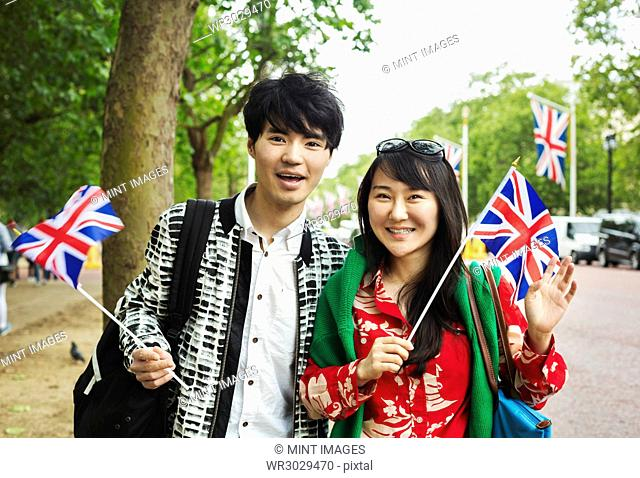 Smiling man and woman with black hair standing on the side of a tree-lined urban road, holding small Union Jack flags, looking at camera