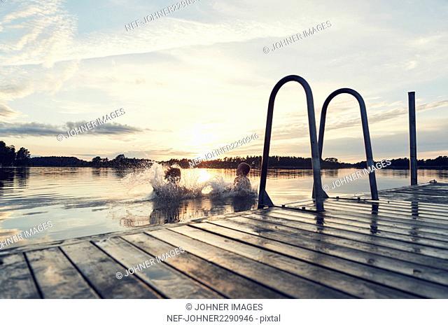 Boys swimming in lake