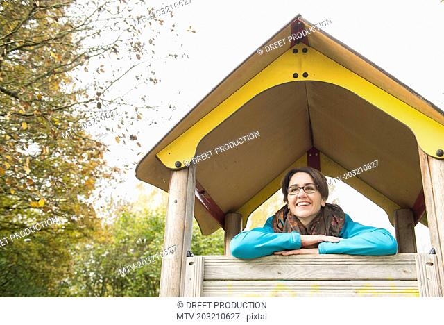 Woman looking out of miniature hut on a playground