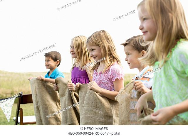 Young cousins lined up to start a potato sack race