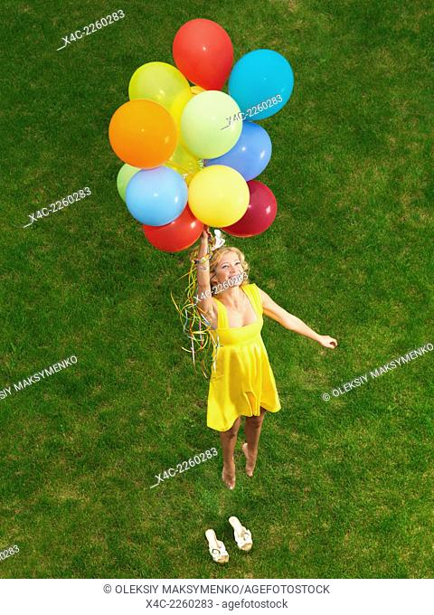 Young happy woman flying up from the ground on colorful air balloons