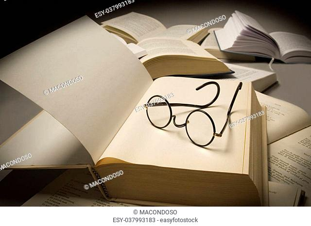 Pair of reading glasses on top of an open book, near other open books