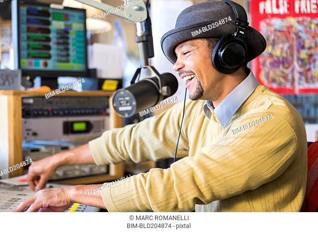 Mixed race disc jockey using turntable in studio