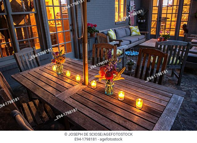 Outdoor table setting on a patio with candles, furniture, and a vase of flowers, Birmingham, Alabama, USA