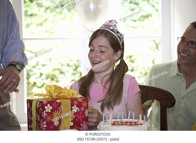 Close-up of a teenage girl opening her birthday present with her father sitting behind her
