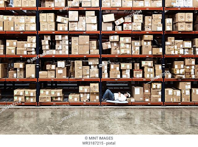 Warehouse worker taking a break next to large racks of cardboard boxes holding product in a distribution warehouse