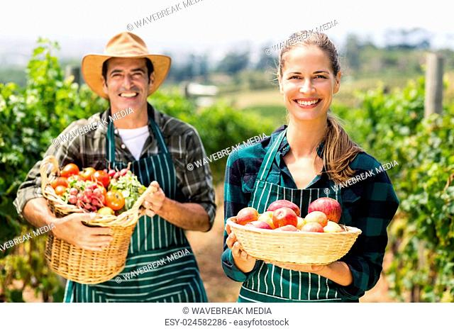 Portrait of happy farmer couple holding baskets of vegetables and fruits