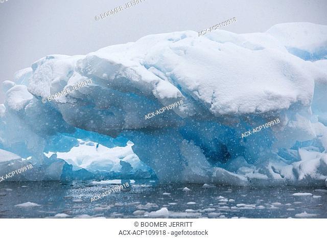 Snow falling on a grounded iceberg near Pleneau Island with its many hues of blue gives the impression of being inside a snowglobe, Pleneau Island