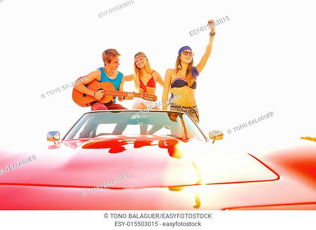 young group having fun on the beach playing guitar and dancing in a convertible car