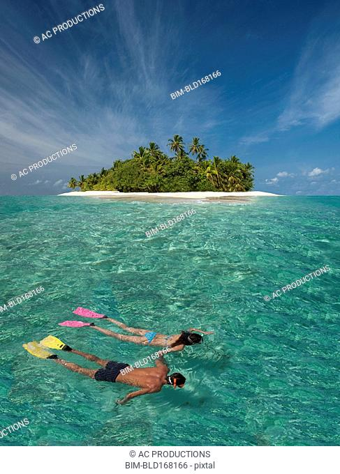 Caucasian couple snorkeling off tropical island