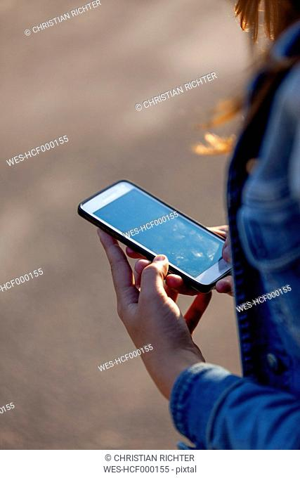 Hands of teenage girl holding smartphone