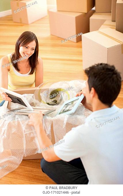 Couple unpacking pictures in new house