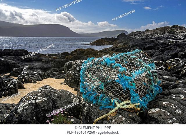 Lobster trap / lobster creel, made of non-degradable plastic and nylon, washed ashore on rocky beach in Scotland, UK