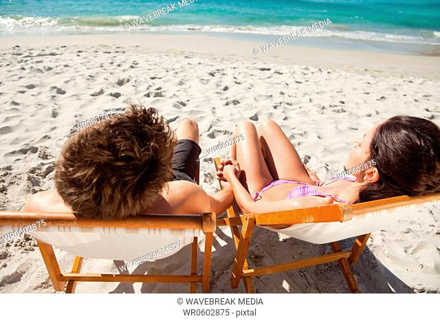 Rear view of a lovers taking a sunbath on deck chairs