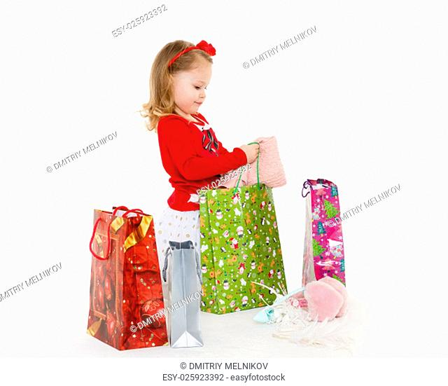 Happy pretty little child with shopping bags sits on a white background. 3 year old