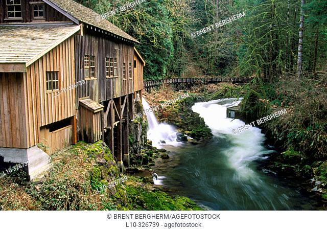 Cedar Creek Gristmill with water spilling out og the flume before it flows inside and powers a grinding stone for grain. Cowlitz County, Washington, USA