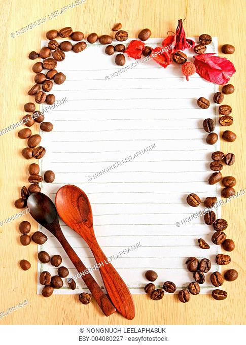 Coffee beans and spoon with paper for notes on the wooden backgr