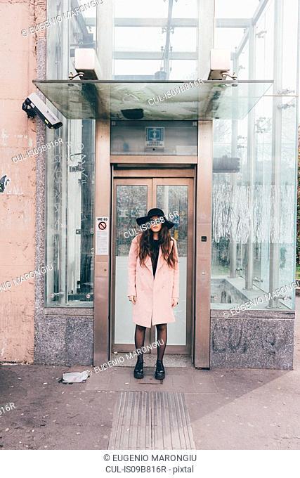 Portrait of young woman standing in doorway