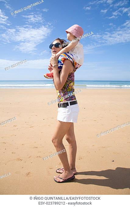 summer family of two years old blonde baby with pink hat white shirt and colorful trousers carrying on shoulders or shouldering of woman mother black sunglasses...