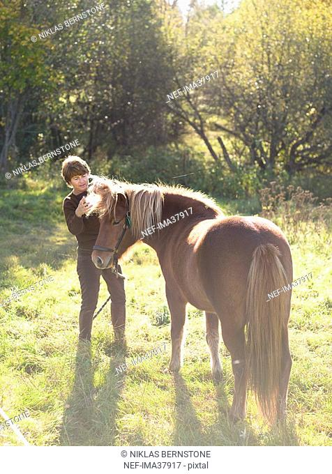 A woman with an Iceland horse in a pasture