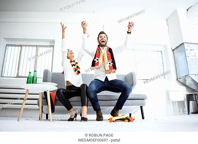 Excited German football fans cheering on couch