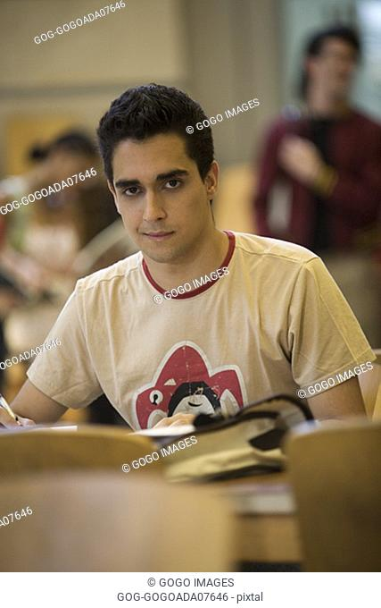 Man studying amidst talking peers